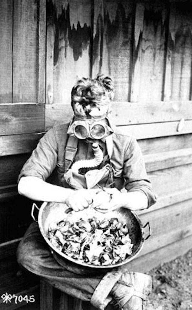 Man working with a gas mask on because of World War I chemical warfare