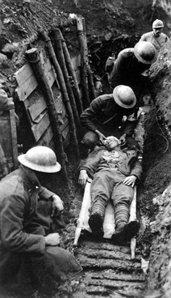 Multiple World War I soldiers in a trench wearing steel helmets